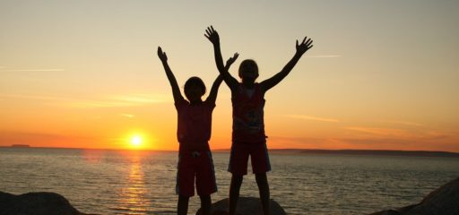 two children raising hands with the sunset behind them